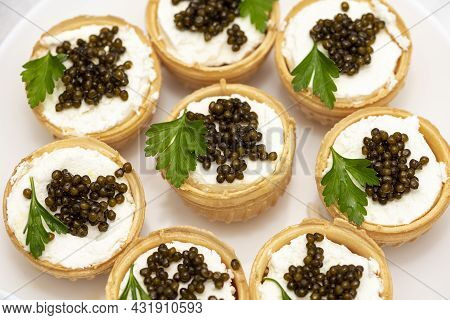 Black Caviar In Tartlets On A Light Background. Healthy Food Concept. Copy Space. Tartlets With Chee