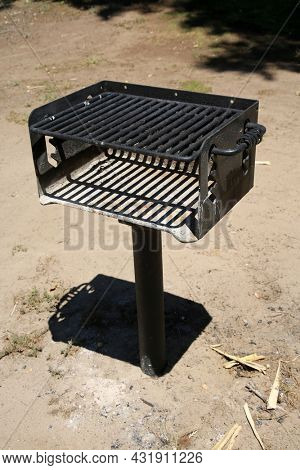 Barbecue Grill. BBQ grill. Hot empty portable barbecue BBQ grill. Waiting for the placement of charcoal and your food. Outdoor Grill in a park.
