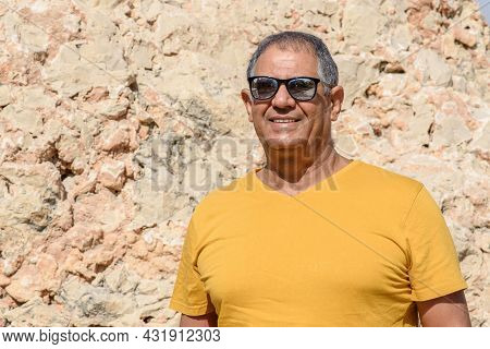 Optimistic Elderly Man Standing And Smiling Outdoor. Close-up Portrait Of Happy Senior Man Looking I
