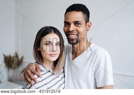 Multiracial Couple In Love Embraces In Cozy Living Room At Home. A Close-up Portrait Of Smiling Cauc