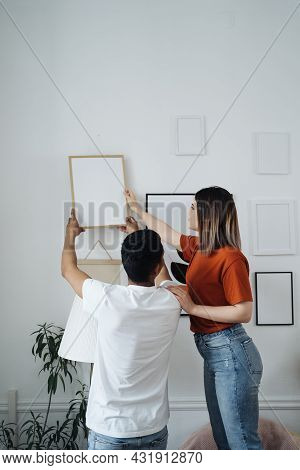 Excited African Young Husband And Caucasian Wife Hang Frame Picture On Wall Happy Settling Together