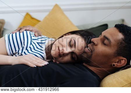 Portrait Of Happy Young African Caucasian Couple Hug Lying On Couch At Home, Mixed Race Husband And