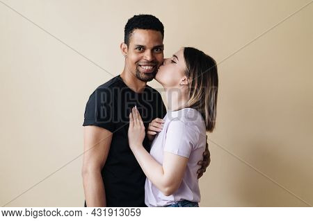 Portrait Of Happy Multiracial Couple Hugging And Posing Together Over Beige Background In Studio, Ro