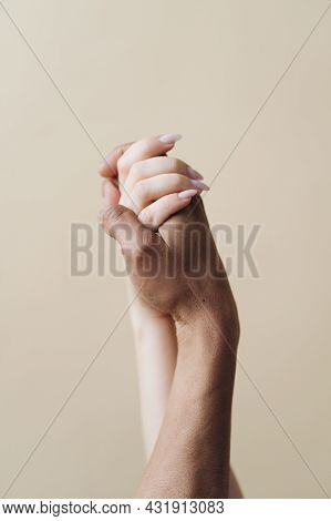 Multiethnic Couple Holding Hands. Young Caucasian Woman And African Male Arms Together On Beige Back