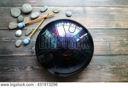 A Musical Instrument, A Glucophone, A Metal Tongue Drum On A Wooden Background. A Modern Musical Ins
