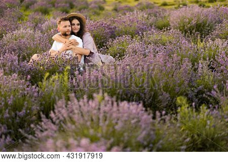 Adorable Beautiful Couple Sitting In The Lavender Field, Hugging, Enjoying Moments Together, Having