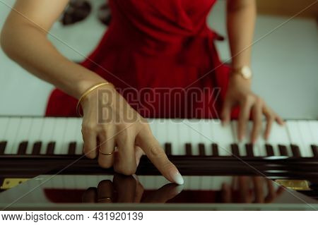 Finger Of Woman Touching On Tablet Computer Screen For Basic Piano Video Lessons While Online Learni
