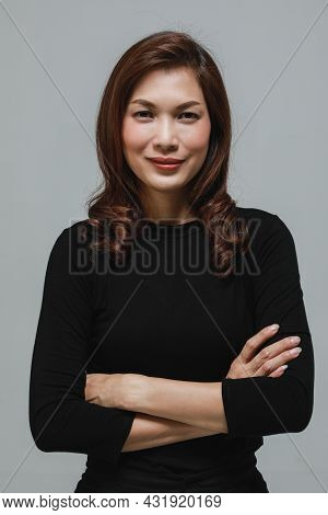 Cute Beautuful Woman In Black Long Sleeves T-shirt Foled Arms And Looking To Camera With Self-confid