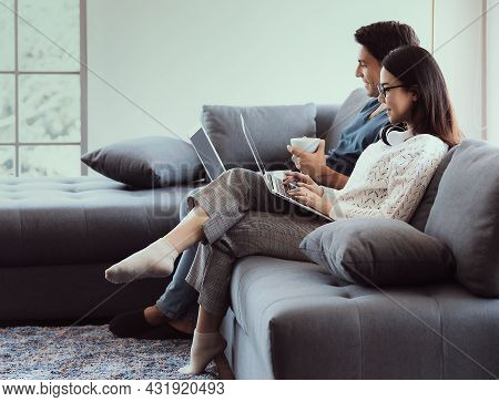 Mix Race Family Lovers, Caucasian Husband And Asian Wife, Sitting In Livingroom Working Via Laptop C