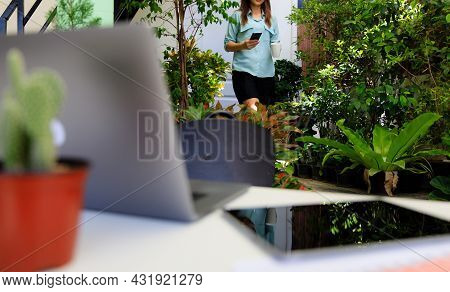 Businesswoman Holding Coffee Cup And Smartphone Walking From Home Room To Working Desk In Corner Sma