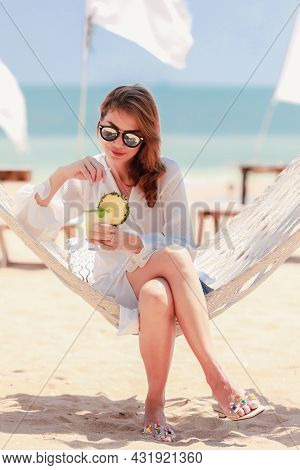 Woman Wearing Sun Protect Sunglasses Drinking Juice In Pineapple Fruit While Sitting On Fabric Swing