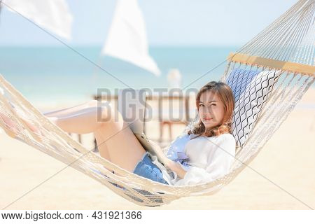 Woman Laying On Fabric Swing On Sand Beach And Using Laptop Notebook Computer Working And Looking To