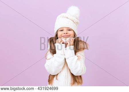 The Child Is Warming Himself On A Warm Sweater. A Little Girl In A White Winter Hat Is Happy And Smi