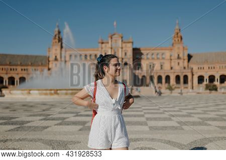 Young Tourist Woman With Glasses Wearing A White Dress And Red Backpack Is Looking Away And Smiling