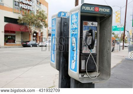 Los Angeles, California - USA - August 27, 2021: An old, dirty coin operated payphone is shown outside along a city sidewalk during a sunny day.  Public Pay Telephone for use by anyone.