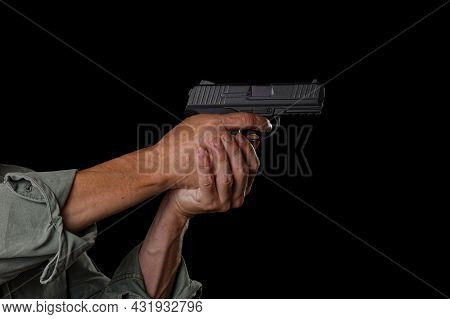 Male Hands Hold A Handgun And Aiming Its To Target. Isolated On Black.