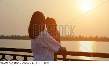 Mother Holds Little Girl Sitting On Railing To Enjoy Bright Sunset On Contemporary City Embankment I