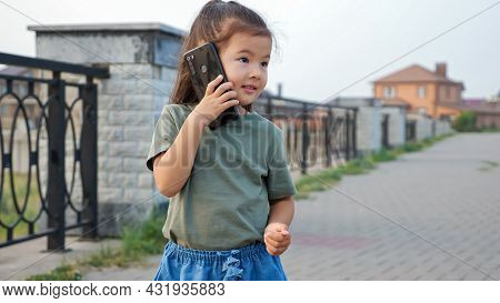 Funny Little Korean Girl With Long Ponytail Talks On Modern Mobile Phone Standing On Empty City Emba