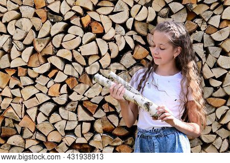 Beautiful Girl With Long Hair In White T-shirt Near Pile Of Firewood. Concept Of Harvesting Firewood