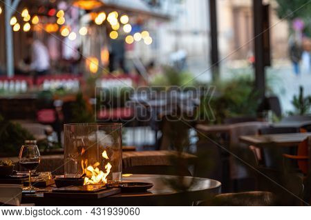 Blurred Photo Of Street Cafe Terrace Decorated With Flame Heate, Evening Street Lights, Fcozy Mood