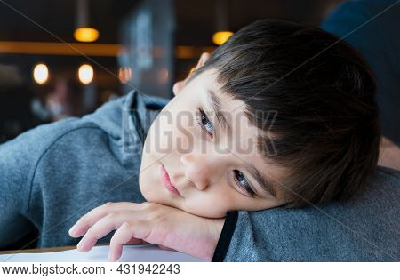 Close Up Face Of Cute Little Child Boy Lying Head On Hands, Candid Shot Mixed Race Kid Sitting Alone