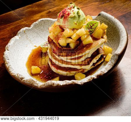 Pancakes with cinnamon powder, crepes and apples on plate.