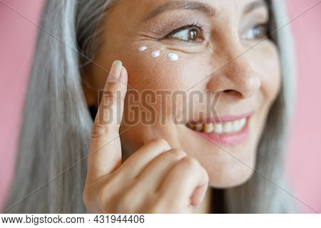 Beautiful Mature Asian Lady Applies Antiaging Cream Under Eye On Pink Background