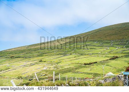 Sloping Hill Patterned By Traditional Dry Stone Wall Dividing The Slope Into Smaller Paddocks For Ag