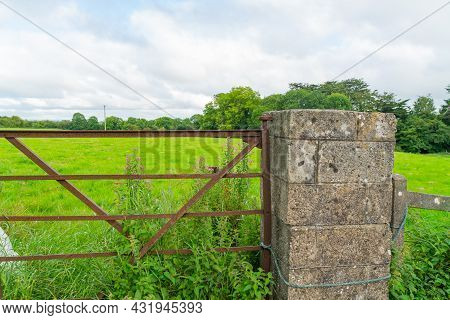 Rural Ireland Green Field Beyond Concrete Post With Wildflowers Through Rusty Iron Gate In County Cl