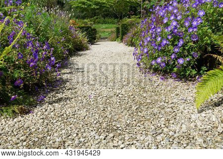 Stony Wide Path Leading Between Flowers And Garden To An Opening At End.