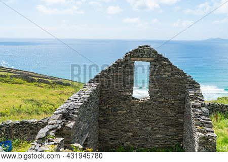 Remains Of Stone Cottage Walls And Window Opening With View To Atlantic Ocean  On Sloping Land Towar