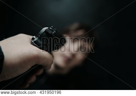 First Person View Of Gun Aimed At Young Man On Black Background. Firearm In Mans Hand. Pov Of Aiming