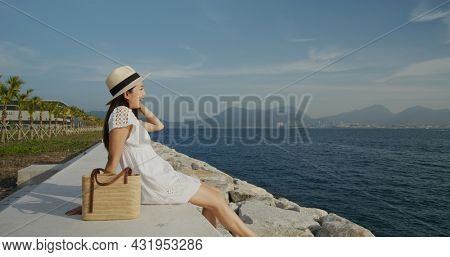 Woman sit on the seaside and enjoy the breeze