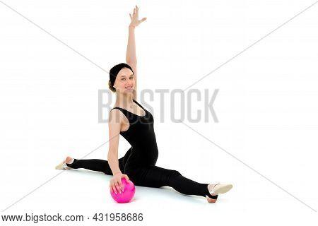Flexible Teenage Girl Doing Gymnastic Split With Ball. Portrait Of Beautiful Girl Gymnast In Black B