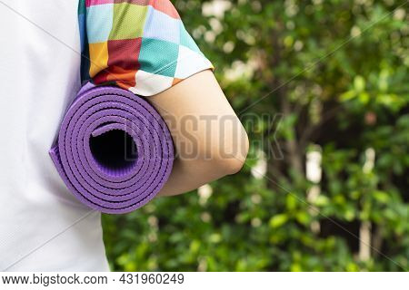 Young Woman Holding A Yoga Mat In Exercise Class For A Sport And Healthy Concept, With Copy Space