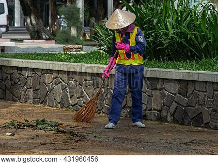 Municipal Worker Sweep The Street With Broomstick. City Street Janitor Makes Sanitation.  Nha Trang,
