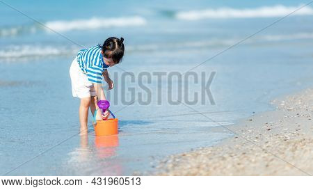 Kid Girl Have Fun And Playing Sand And Water At Tropical Beach. Family Child Tourism Travel Enjoy An