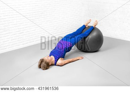 Reverse Plank With Exercise Ball. Caucasian Slim Woman In Blue Sportswear Does Workout In Fitness St