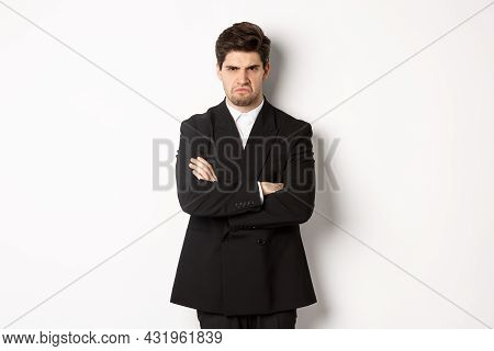Portrait Of Angry Handsome Man In Black Suit, Cross Arms On Chest And Looking Offended, Frowning And