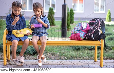 Back To School. Cute Little School Girls Sitting On Bench In School Yard And Eating Lunch Outdoor. R
