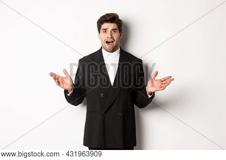 Portrait Of Confused And Worried Handsome Man In Suit, Looking At Something Strange, Spread Hands Si
