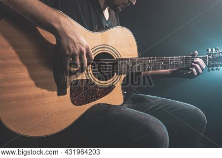 Close-up Of A Man Playing An Acoustic Guitar In The Dark With Stage Lighting.