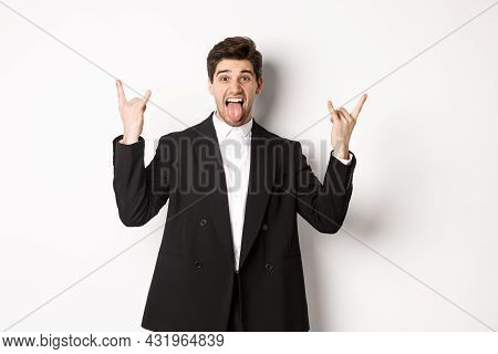 Portrait Of Happy Attractive Guy Having Fun At Party, Wearing Black Suit, Showing Rock-n-roll Sign A