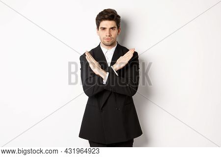 Portrait Of Serious And Concerned Man In Black Suit, Showing Stop Gesture And Frowning, Making Cross