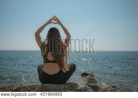 Woman Makes Heart With Hands On Beach. Young Woman With Long Hair, Fitness Instructor, Stretching Be