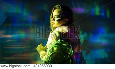 Virtual reality, city of the future. Beautiful cyber girl in hi-tech clothes of the future stands in the neon light of the night cyber city.