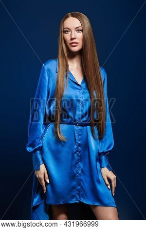 Fashion shot. Beautiful fashion model girl with long straight hair poses in blue satin dress on a dark blue background.