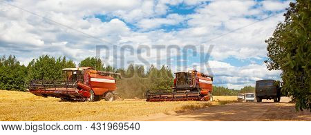 Combine Harvesters In The Field For Harvesting Wheat. Special Equipment On The Field. Road Along The