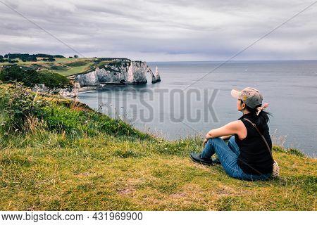 Woman contemplating the Etretat bay landscape, Normandy, France