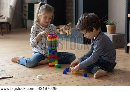 Two Sibling Children Completing Tower Model Form Plastic Building Blocks